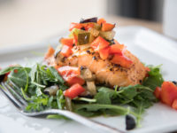 Salmon on a bed of arugula topped with a pickle, blueberry, and red pepper relish. using Prissy Pickles Sweet Pickles.